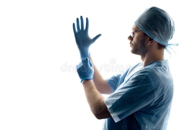 Cirujano en guantes que llevan uniformes médicos en blanco imagenes de archivo