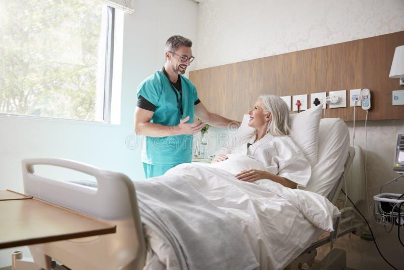 Cirujano Visiting And Talking con el paciente femenino maduro en cama de hospital foto de archivo