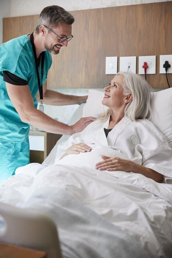 Cirujano Visiting And Talking con el paciente femenino maduro en cama de hospital imagenes de archivo