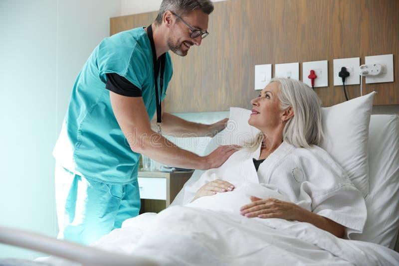 Cirujano Visiting And Talking con el paciente femenino maduro en cama de hospital fotografía de archivo libre de regalías