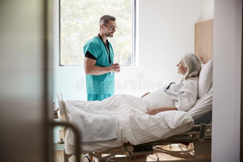 Cirujano Visiting And Talking con el paciente femenino maduro en cama de hospital fotos de archivo libres de regalías