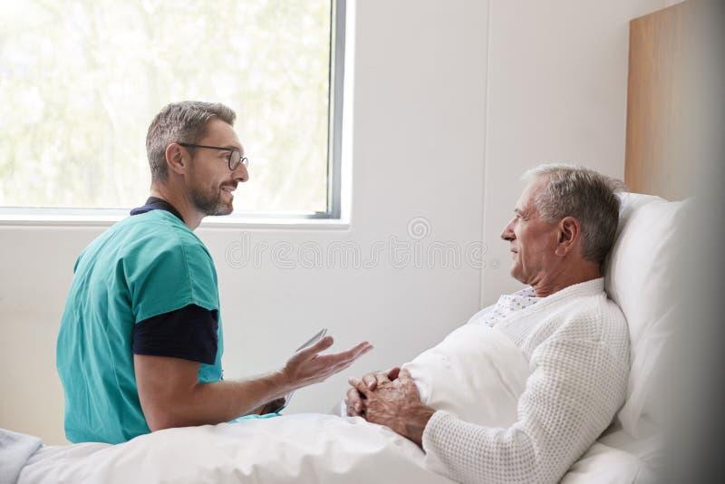 Cirujano Visiting And Talking con el paciente masculino mayor en cama de hospital en unidad geriátrica foto de archivo