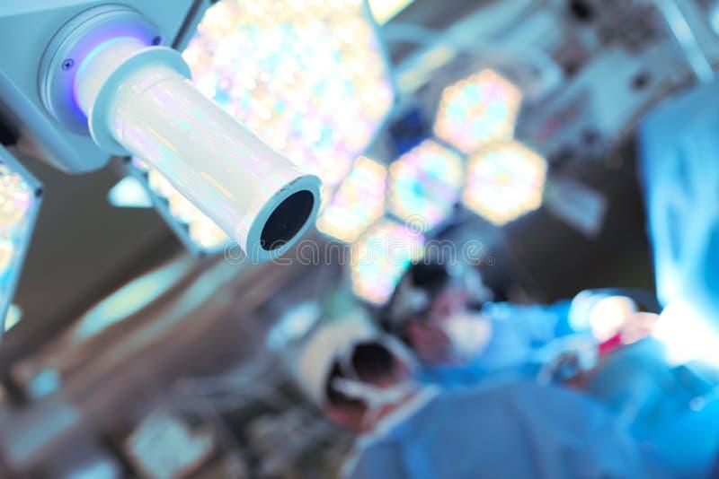 Cirujanos borrosos en la sala de operaciones y el cierre-u quirúrgico de la lámpara imagenes de archivo