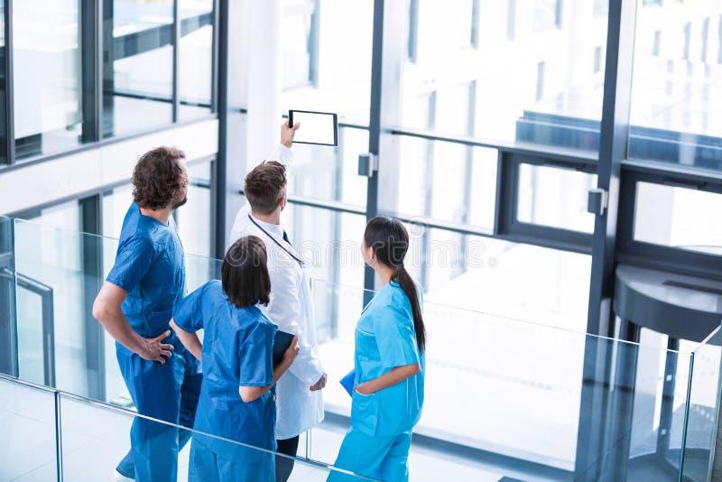 Cirujanos, doctor y enfermera mirando la tableta digital fotografía de archivo