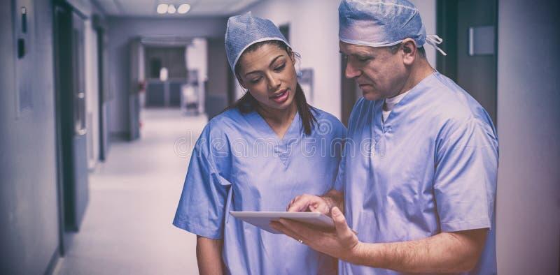 Cirujanos que discuten sobre la tableta digital foto de archivo libre de regalías