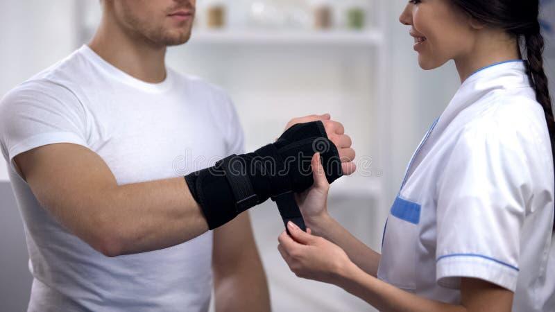Cirurgião fêmea de sorriso que aplica o paciente masculino da cinta do pulso do titã, reabilitação fotos de stock royalty free