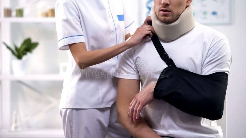 Cirurgião fêmea que ajusta o estilingue paciente masculino do braço, a ortopedia e o período da reabilitação fotografia de stock royalty free