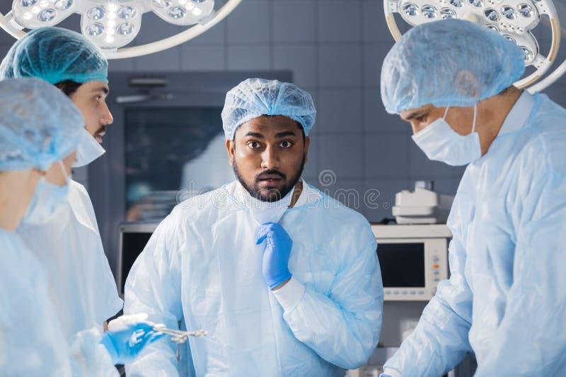 Cirurgião indiano que olha chocado extremamente durante a operação cirúrgica imagens de stock royalty free