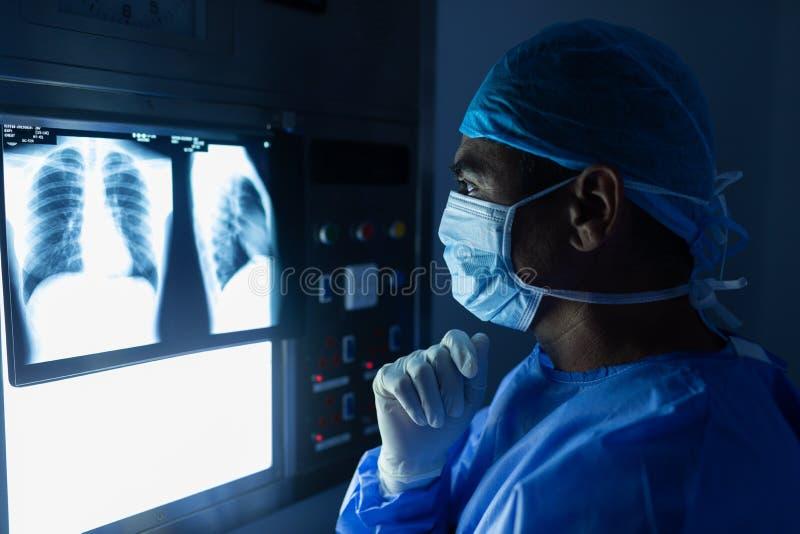 Cirurgião masculino que lê o raio de x na sala de operações no hospital fotografia de stock royalty free