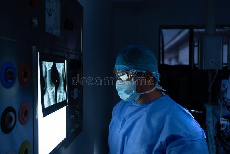 Cirurgião masculino que lê o raio de x na sala de operações no hospital fotos de stock royalty free