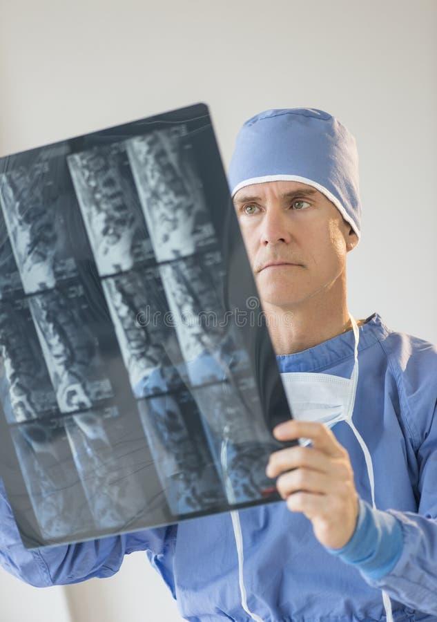 Cirurgião masculino In Uniform Looking no raio X fotos de stock royalty free