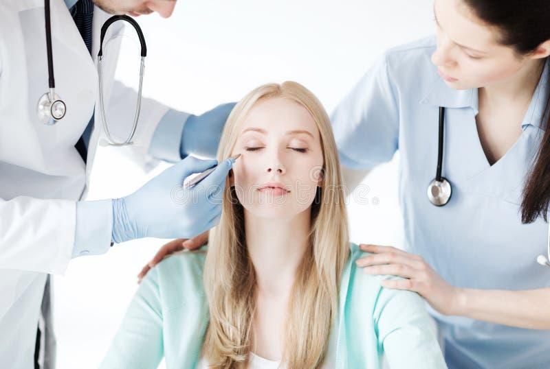 Cirurgião plástico e enfermeira com paciente imagem de stock