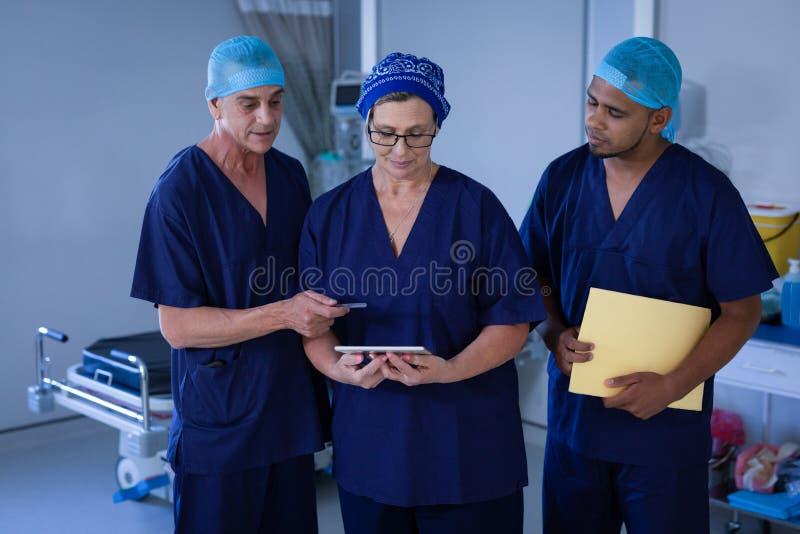 Cirurgiões que discutem sobre a tabuleta digital no hospital foto de stock
