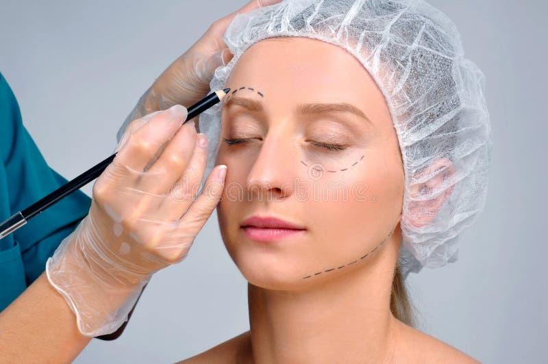 Cirurgia plástica Mulher com linhas de perfuração sobre sobre a sobrancelha Tratamento e face lift antienvelhecimento imagens de stock royalty free