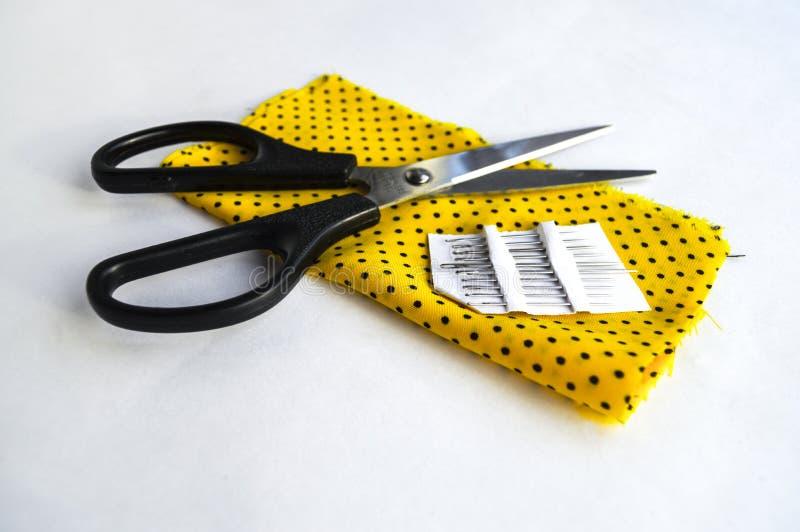 Ciseaux et aiguille sur le tissu jaune images stock
