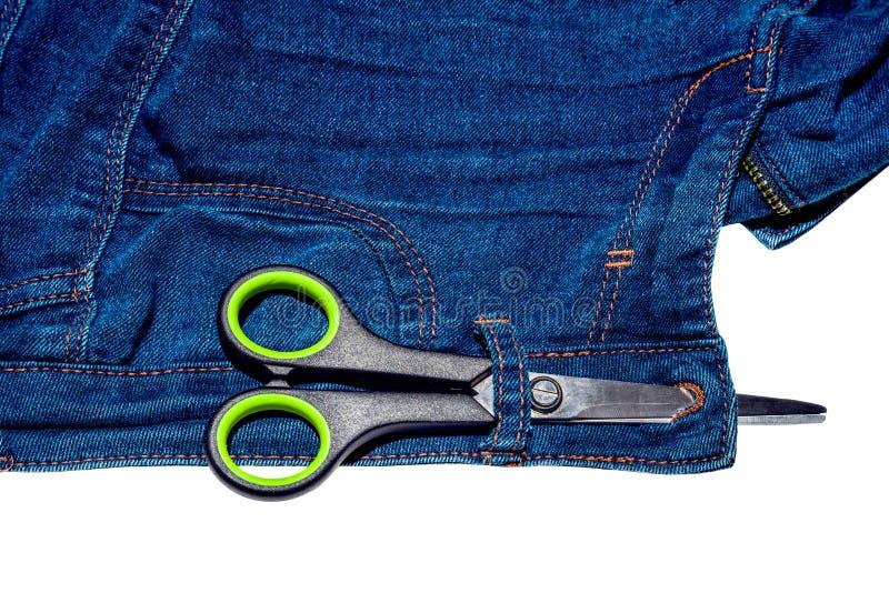 Ciseaux et blues-jean et tirette d'isolement sur le fond blanc photo stock