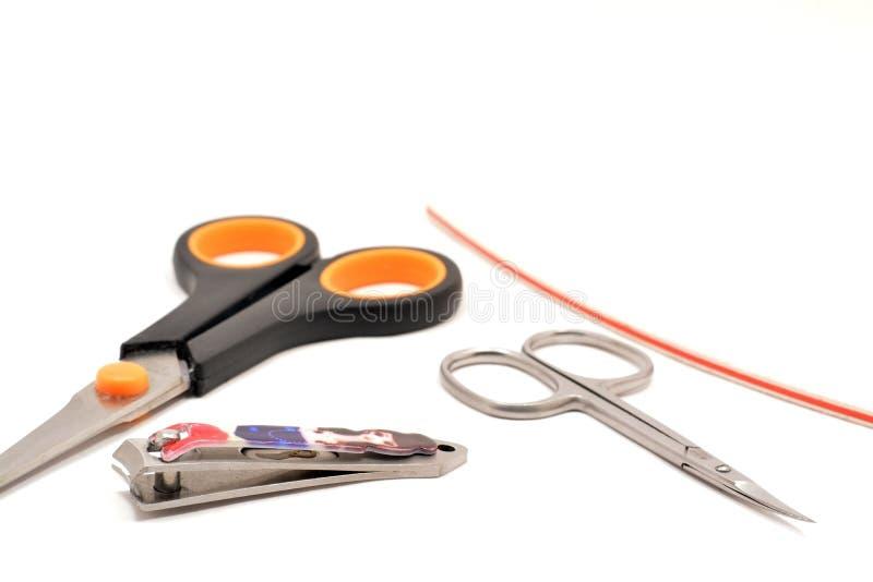 Ciseaux pour des clous de coupe et accessoires d'isolement sur le fond blanc photos stock
