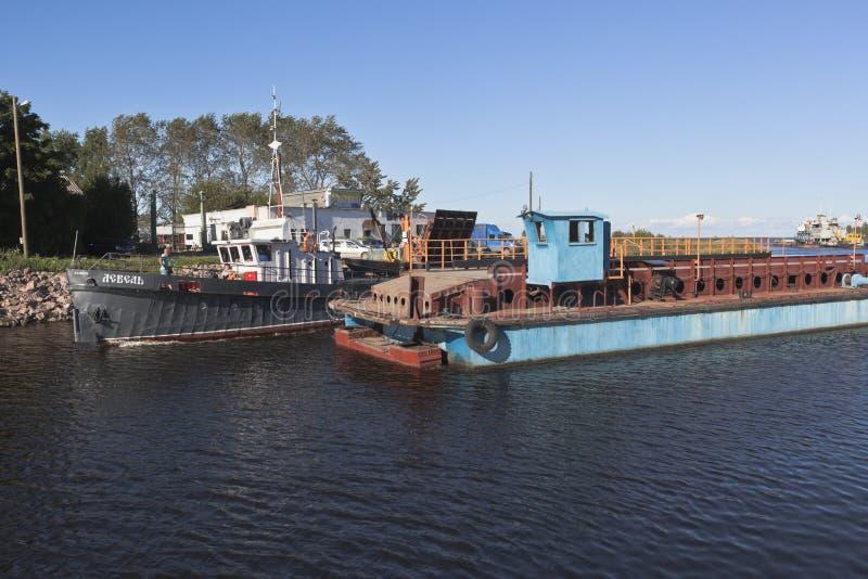A cisne incorporada do barco de trabalho passa com o Ilinskiy divorciado ponte na cidade de Belozersk foto de stock royalty free