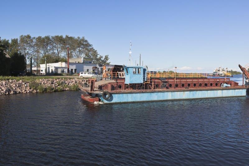 A cisne incorporada do barco de trabalho passa com o Ilinskiy divorciado ponte na cidade de Belozersk, região de Vologda imagens de stock
