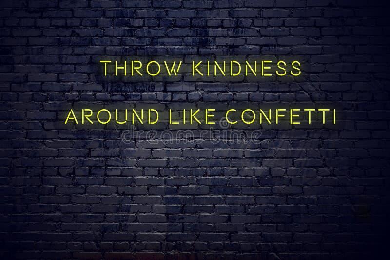 Cita??es inspiradores positivas no sinal de n?on contra a bondade do lance da parede de tijolo ao redor como confetes ilustração do vetor