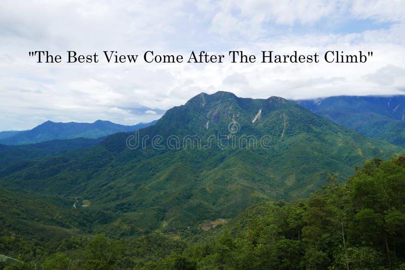 Cita de la motivación la mejor visión venida después de la subida más dura con la opinión de la montaña y de cielo azul foto de archivo libre de regalías