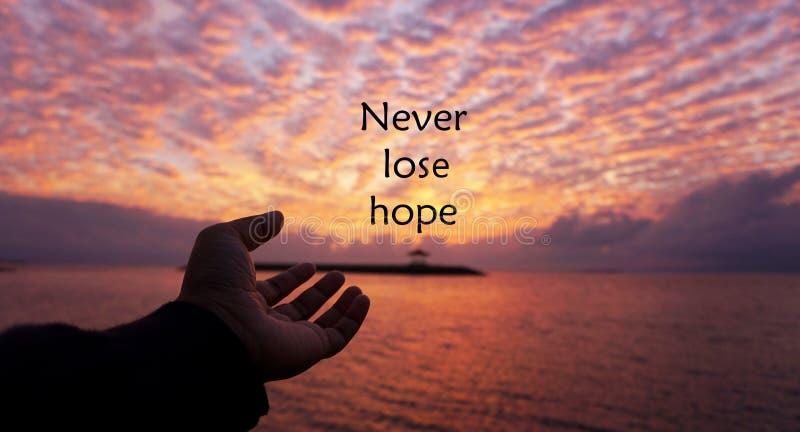 Cita inspirada de la esperanza - nunca perder esperanza Con una mano humana abierta alcanzando el sol para presentarse Con puesta fotos de archivo libres de regalías