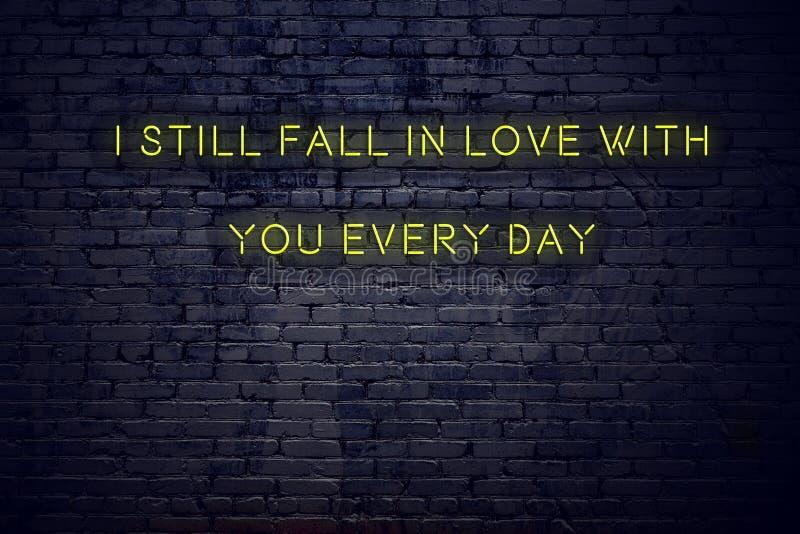 Cita inspiradora positiva en señal de neón contra la pared de ladrillo todavía caigo en amor con usted cada día stock de ilustración