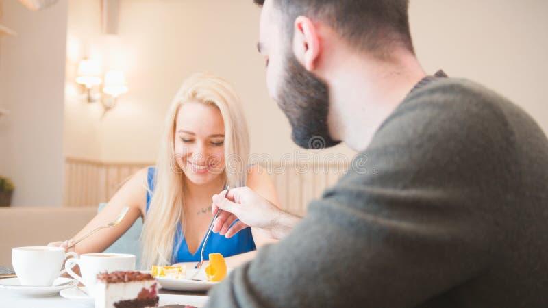 Cita romántica, individuo que come el postre del girll s en un café fotografía de archivo