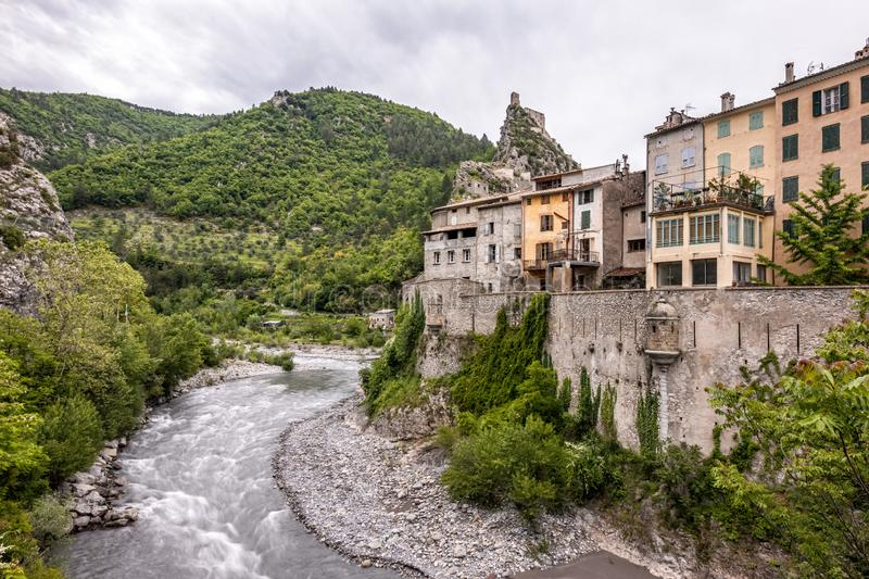The citadel of Entrevaux and Var river in France. The medieval citadel of Entrevaux sits high on a rocky outcrop above the town and the Var valley in the Alpes stock photography