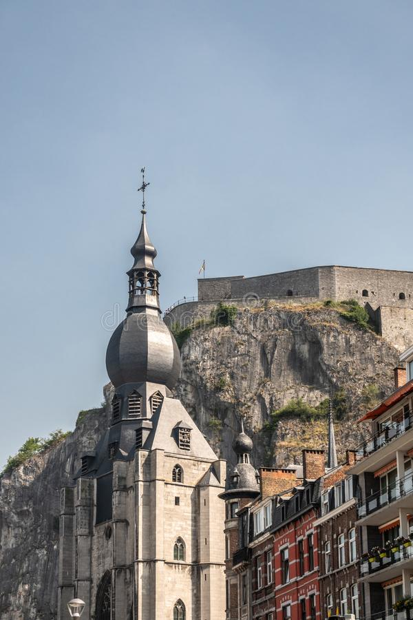 The Citadel towers high above the spire of Notre Dame Church, Dinant, Belgium. Dinant, Belgium - June 26, 2019: The citadel fort on cliff towers high above the royalty free stock image