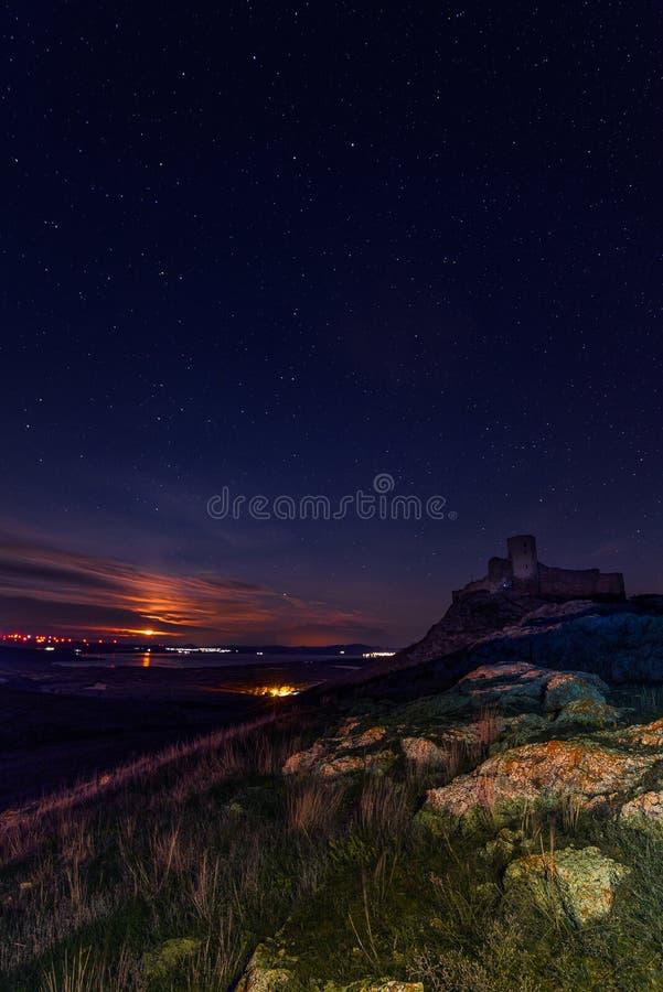 Citadela antiga sobre um monte rochoso durante a noite em um céu estrelado com o ajuste da lua atrás de algumas nuvens com rocha  imagem de stock