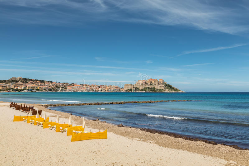 A citadela de Calvi com sunbeds alinhou na praia em Córsega imagens de stock royalty free