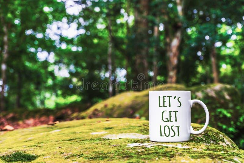 Citation inspirée de voyage - Let' ; s obtiennent perdu sur la tasse blanche Fermez-vous vers le haut de la tasse blanche pou image libre de droits