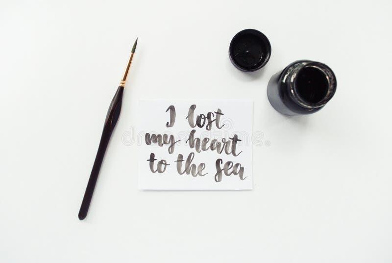 Citation inspirée j'ai perdu mon coeur à la mer, l'encre, pinceau sur un fond blanc Espace de travail d'artiste image stock