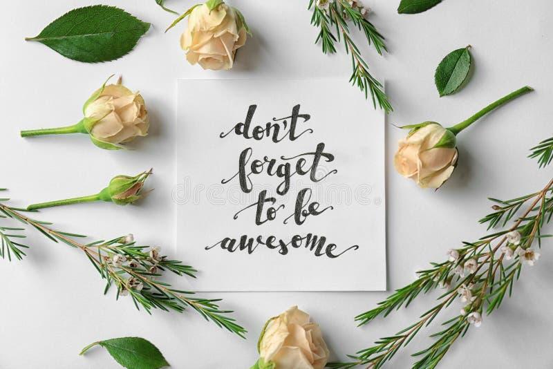 Citationstecken` glömmer inte att vara enorm ` som är skriftlig på papper med rosor och sidor på vit bakgrund arkivfoto