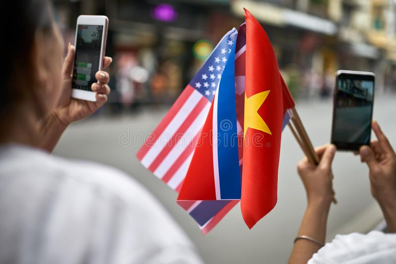 People with flags taking photos of diplomatic escort car passage. Citizens are holding flags of the USA and Vietnam while taking photos on their cellphones royalty free stock image