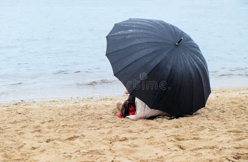Citoyen avec un parapluie se reposant sur le rivage arénacé images stock