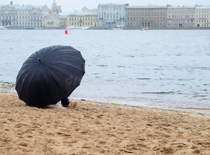 Citoyen avec un parapluie se reposant sur le rivage arénacé photos stock
