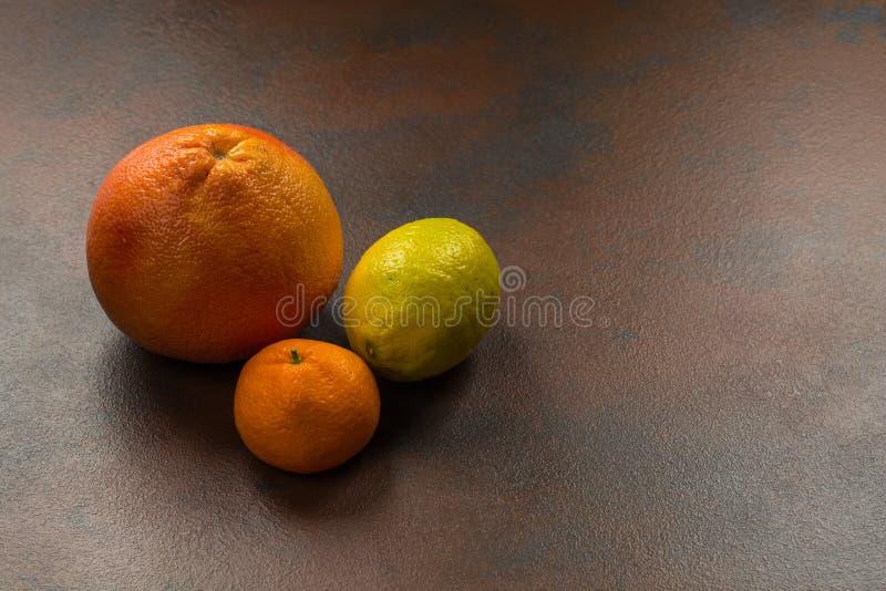 Citrinas: laranja, limão, tangerina no fundo de pedra escuro fotografia de stock