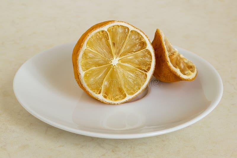 Citroen droog in de koelkast Oude citrusvrucht op een witte schotel Voedsel in de huisijskast die wordt vergeten royalty-vrije stock foto