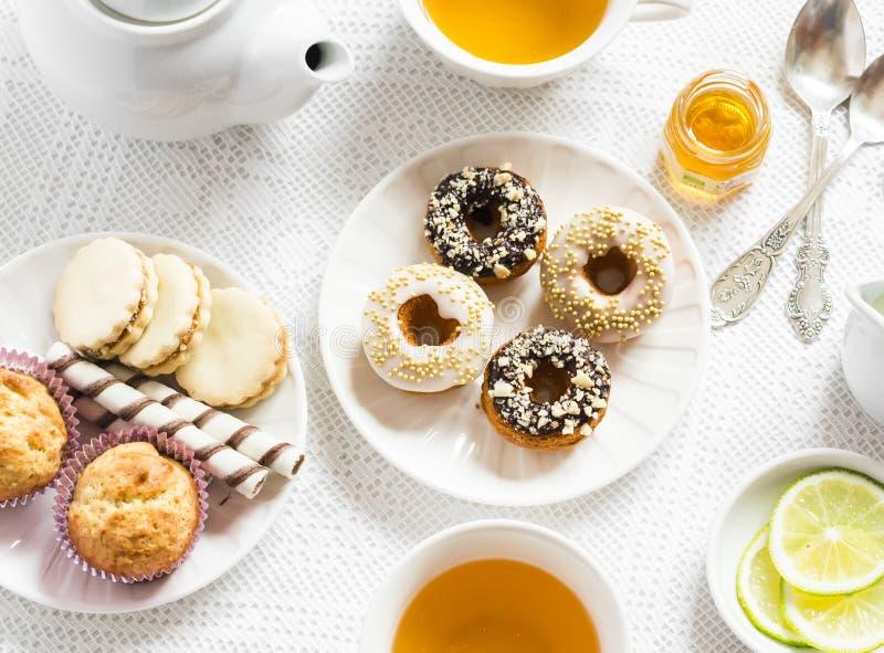 Citroen groene thee en snoepjes - banaanmuffins, koekjes met karamel en noten, donuts met chocolade en citroenglans, theestel op  stock afbeeldingen