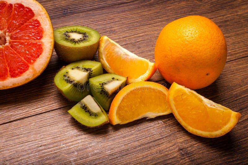 Citroen, sinaasappel, kiwi, grapefruit, mandarin op een houten oppervlakte regeling van gesneden fruit Hoogste mening met exempla stock fotografie