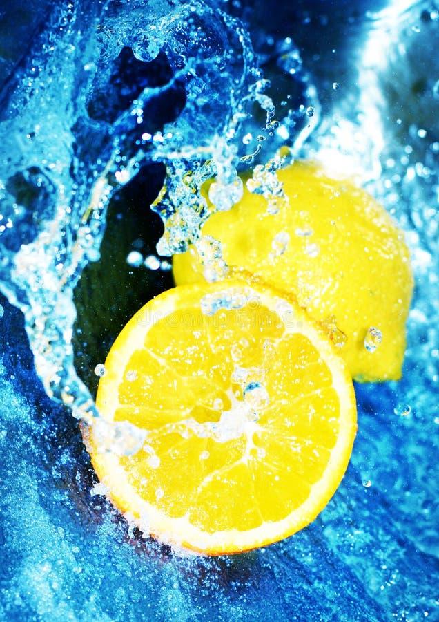 Citroenen in blauw water stock foto's
