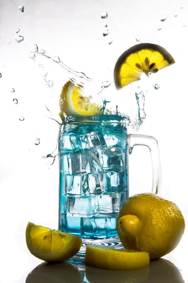Citroenen die in een glas blauw ijswater met plonsen tegen geïsoleerd op witte achtergrond vallen Verfrissende drank stock foto