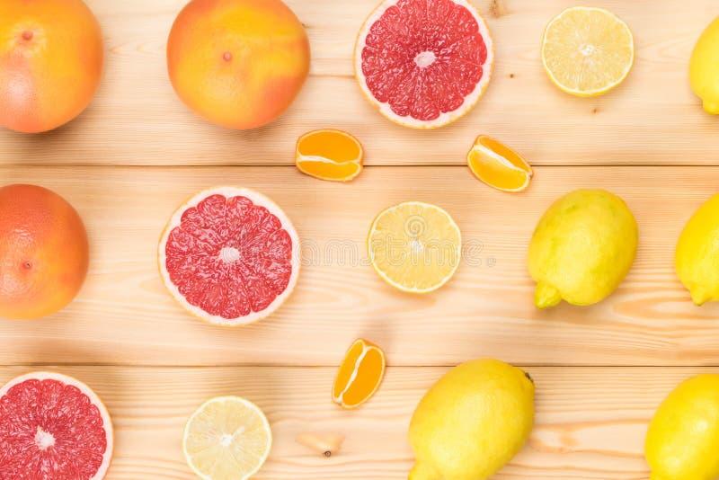 citroenen en grapefruits en stukken van sappige citrusvrucht op een lichte houten raad stock foto's