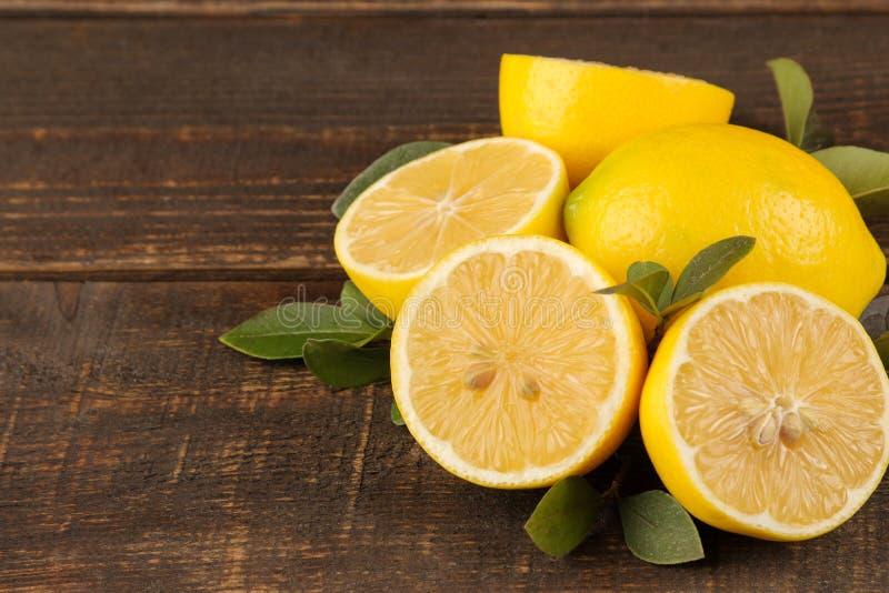 Citroenen en kalk Verse citroen met bladeren en citroenplakken op een bruine houten lijst Close-up royalty-vrije stock fotografie