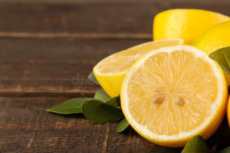 Citroenen en kalk Verse citroen met bladeren en citroenplakken op een bruine houten lijst Close-up stock foto's
