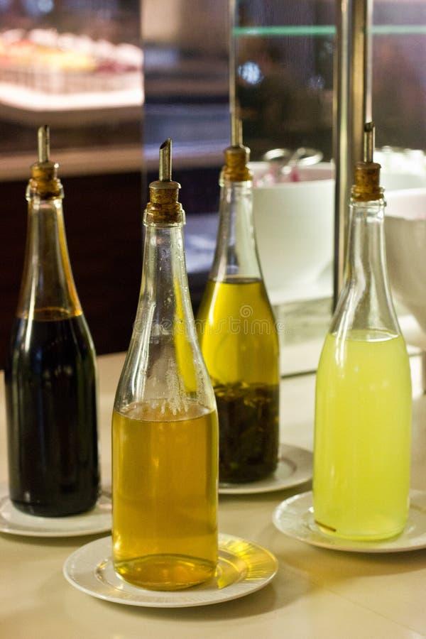 Citroensaus, azijn, granaatappelsaus en olijfolie in glas B royalty-vrije stock afbeeldingen