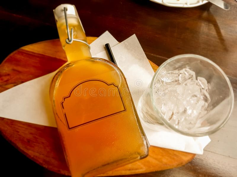 Citroenthee in een fles en een glas van ijs op houten dienblad stock afbeeldingen