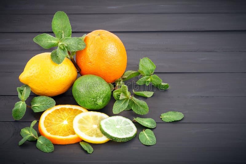 Citron, apelsin och limefrukt på en darkphone som göras av trä royaltyfria bilder